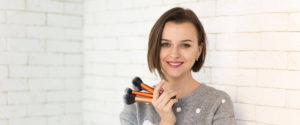 Smiling girl holding makeup brushes